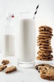 selektivní zaměření skla s čerstvým mlékem a slámou blízké čokoládovým koláčkům a láhev na mramorový stůl