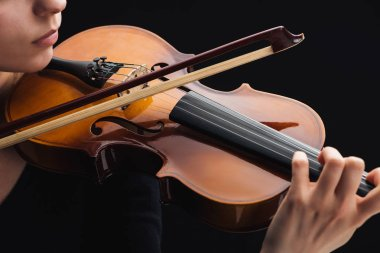 cropped view of woman playing cello with bow isolated on black