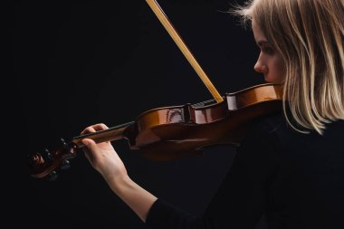 young concentrated woman playing cello with bow isolated on black with copy space