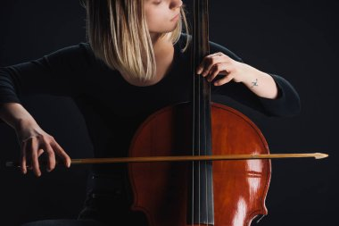 partial view of tattooed woman playing double bass in darkness isolated on black