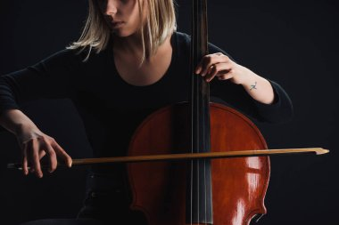 cropped view of tattooed woman playing double bass in darkness isolated on black