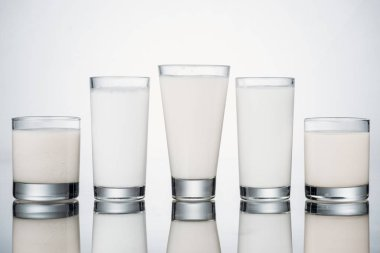 Row of glasses with organic fresh alternative milk on grey background with reflection stock vector