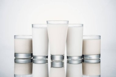 Glasses with organic alternative milk on grey background with reflection stock vector