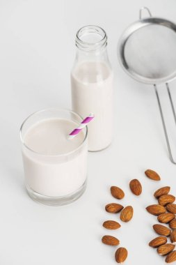 organic almond milk in bottle and glass with straw near scattered almonds and sieve