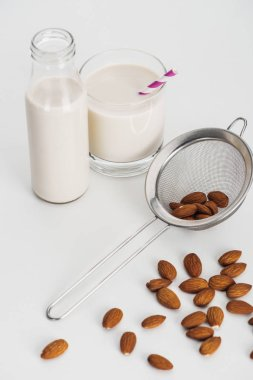 vegan almond milk in bottle and glass with straw near scattered almonds and sieve