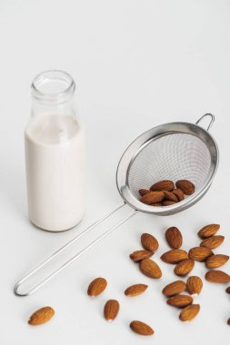 vegan almond milk in bottle near scattered almonds and sieve on grey background