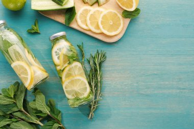 top view of detox drink in bottles with lemon and cucumber slices, mint and rosemary