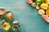 Drinks im Glas mit Obst, Gemüse, Kräutern, Beeren und Grün in der Nähe von Fruchtzutaten auf blauer Holzoberfläche