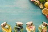 Fotografie Draufsicht auf Entgiftungsgetränke in Gläsern mit Obst, Gemüse, Kräutern, Beeren und Grün in der Nähe von Fruchtzutaten auf blauer Holzoberfläche