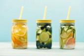 Fotografie Bio-Entgiftungsgetränke mit Beeren, Obst und Gemüse in Gläsern mit Strohhalmen auf blauem Grund