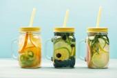 Bio-Entgiftung Getränke mit Beeren, Früchten und Kräutern in Gläsern mit Strohhalmen isoliert auf blau