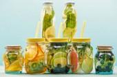 organické detoxinové nápoje s bobulovinami, ovocem a zeleninou ve skleničkách a lahvích se šlemi izolovanými na modrém