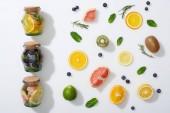 Drinks in Gläschen in der Nähe von Fruchtscheiben, Blaubeeren, Minze und Rosmarin