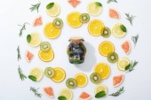 flat lay with sliced kiwi, oranges, lemons, grapefruits, mint, rosemary and detox drink in jar