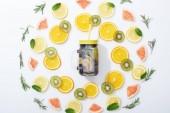 Flachlage mit Kiwi, Orangen, Zitronen, Grapefruits, Minze, Rosmarin und Entgiftungsgetränk im Glas auf grauem Hintergrund