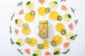 flache Lage mit geschnittenen Kiwi, Orangen, Zitronen, Grapefruits, Minze, Rosmarin und Entgiftungsgetränk im Glas mit Stroh auf grauem Hintergrund