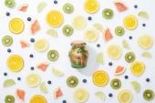 pohled na detoxinovou skleničku ve sklenici mezi nakrájené ovoce a borůvky na bílém pozadí