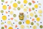 pohled na přírodní detoxový nápoj v nádobě mezi nakrájené ovoce a borůvky na bílém pozadí