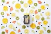 pohled na detoxinovou skleničku ve sklenici se slámou mezi nakrájené ovoce a borůvkami na bílém pozadí