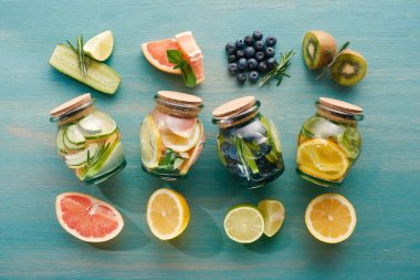 top view of detox drinks in jars with citrus fruits, berries and cucumbers