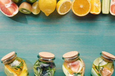 top view of detox beverages in jars with fruits, vegetables, herbs, berries and greenery near ingredients on wooden blue surface