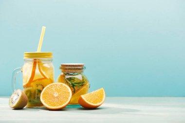 organic fruit detox drinks in jars near oranges and kiwi isolated on blue