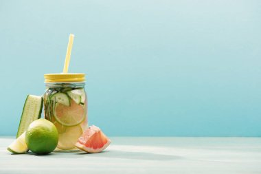 fresh detox drink in jar near limes, cucumber and grapefruit isolated on blue