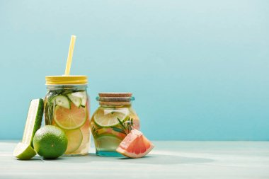 fresh detox drinks in jars near limes, cucumber and grapefruit isolated on blue