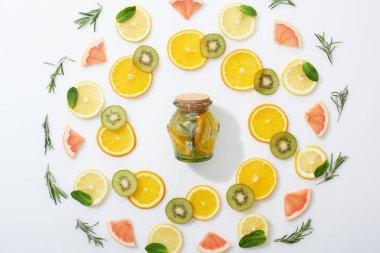 top view of sliced kiwi, oranges, lemons, grapefruits, mint, rosemary and detox drink in jar on grey background