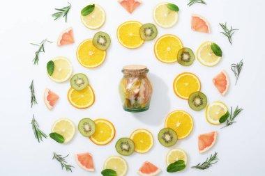 flat lay with fresh sliced kiwi, oranges, lemons, grapefruits, mint, rosemary and detox drink in jar