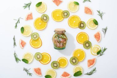 Flat lay with sliced kiwi, oranges, lemons, grapefruits, mint, rosemary and fresh detox drink in jar on grey background stock vector