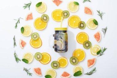 flat lay with sliced kiwi, oranges, lemons, grapefruits, mint, rosemary and detox beverage in jar on grey background