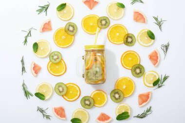 flat lay with sliced kiwi, oranges, lemons, grapefruits, mint, rosemary and detox drink in jar with straw on grey background