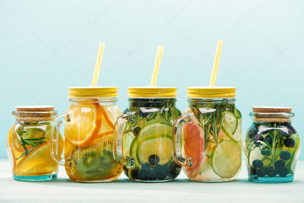 Fresh detox drinks with berries, fruits and vegetables in jars with straws isolated on blue stock vector