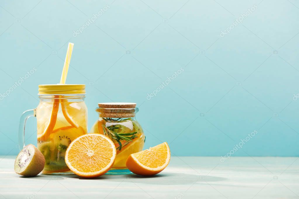 Organic fruit detox drinks in jars near oranges and kiwi isolated on blue stock vector