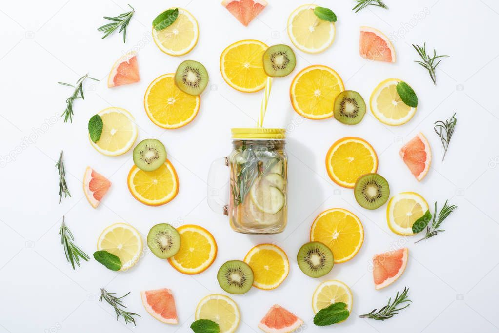 Flat lay with sliced kiwi, oranges, lemons, grapefruits, mint, rosemary and detox drink in jar on grey background stock vector
