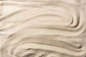 Photo top view of textured sandy beige background with smooth waves