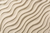 top view of beige sandy backdrop with smooth waves
