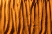 zobrazení texturovaného plážového písku s vlnami a oranžovým filtrem