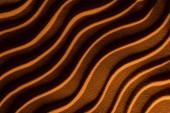 horní pohled na texturované písek s vlnami a oranžovým filtrem