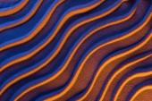 zobrazení texturovaného písku s hladkými vlnami a neonově barevným filtrem