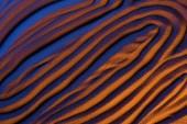 Fotografie pohled na abstraktní texturované pozadí s pískem, hladkými vlnami a barevným filtrem