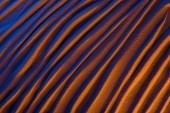 pohled shora na abstraktní vlnité pozadí s pískem a barevným filtrem