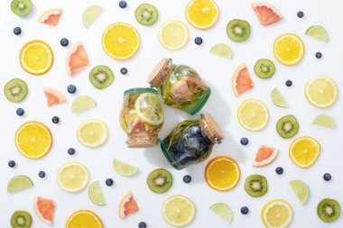 top view of three detox drinks in jars among sliced fruits and blueberries on white background