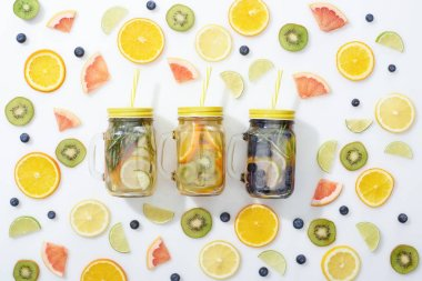 Top view of detox drinks in jars with straws among sliced fruits and blueberries on white background stock vector