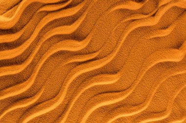 top view of textured sand with smooth waves and orange color filter
