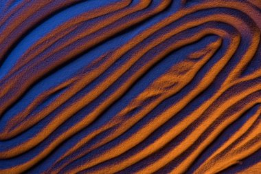 top view of abstract textured background with sand, smooth waves and color filter