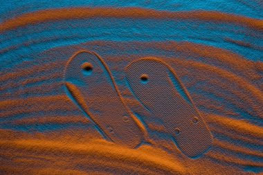 top view of flip flops mark on textured sand with color filter