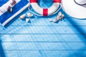 top view of striped towel, sunglasses, lifebuoy, white floppy hat and seashells on blue wooden background with shadows and copy space