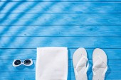 top view of white folded towel, retro sunglasses and flip flops on blue wooden background with shadows and copy space